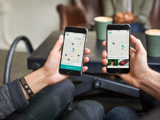 Users looking at the Lyft mobile app, a ride-sharing