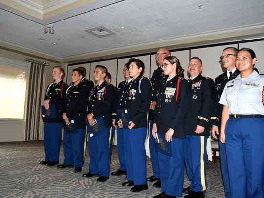 Six JROTC cadets, and their instructors, pose for a