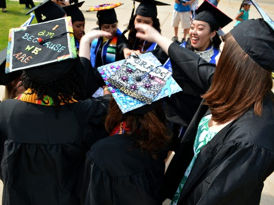A group of Lawrence University students huddle up outside Memorial Chapel before their graduation ceremony Sunday.