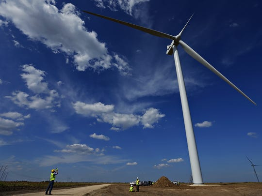 An individual photographs a wind turbine during a September 2016 tour of a wind farm in Blackwell, Oklahoma. City Utilities purchases power generated by the turbines.