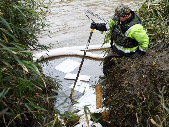 Brad Rogers, of Mountain Environmental Services, steps into the French Broad River to replace absorbent pads across the street from Mountain Energy February 7, 2018, where it is estimated thousands of gallons of petroleum fuel spilled into the river.