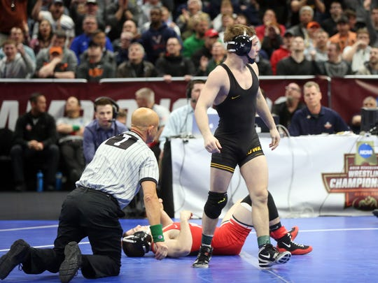 Iowa associate head coach Terry Brands celebrates with assistant coach Ben Berhow as Spencer Lee pins Ohio State's Nathan Tomasello in the 125 semifinals at the NCAA Wrestling Championships at Quicken Loans Arena in Cleveland, Ohio on Friday, March 16, 2018.