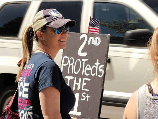 Melissa Porter, 42, carries a sign as she participates