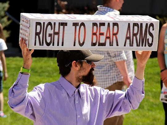Greg Ross, 28, holds a sign at a pro gun rally in Carson