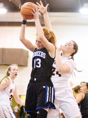 Western Mennonite's Madison Hull pulls down a rebound contested by Monroe's Emily Stahl.