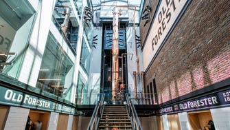 At the front, visitors are welcomed by the column still and a retail shop on the ground floor. The glass-walled elevator is seen behind the still.