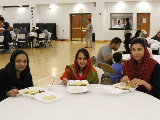 Community members enjoy a meal after sunset during