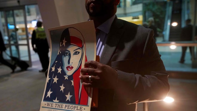 """A protester holds a """"We the People"""" sign during a rally against the travel ban at San Diego International Airport on March 6 in San Diego.   US President Donald Trump signed a revised ban on refugees and on travelers from six Muslim-majority nations, scaling back the order to exempt Iraqis and permanent US residents. / AFP PHOTO / Sandy HuffakerSANDY HUFFAKER/AFP/Getty Images"""