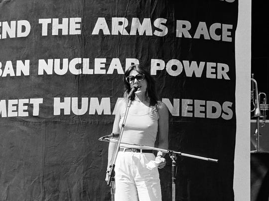 Patti Davis, daughter of President Ronald Reagan stands in front of a banner urging the ban of nuclear power during a sold-out fund-raising anti-nuclear rally Sunday June 14, 1981 in Los Angeles, Calif. Nearly 18,000 people heard the young actress plea to spread the message across the country during the benefit concert sponsored by the Southern California Alliance for survival. (AP Photo/Lennox McLendon)