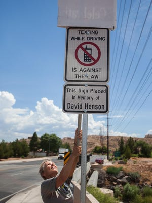 Leslee Henson reveals a new sign warning against distracted driving near a spot where she and her husband, David, were struck by a driver who was texting on Thursday, July 25, 2013.