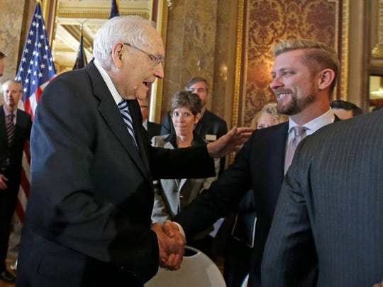Elder L. Tom Perry, left, of the Church of Jesus Christ of Latter-day Saints Quorum of the Twelve Apostles shakes hands with Equality Utah executive director Troy Williams after Utah lawmakers introduced a landmark anti-discrimination bill during a news conference at the Utah State Capitol, in Salt Lake City.