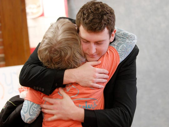 Luke Metzler gets a hug Saturday from family friend