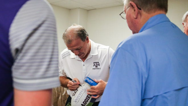 Texas A&M University head coach Jimbo Fisher signs a football before his lecture during the Angelo Football Clinic Tuesday, June 12, 2018, at Junell Center.