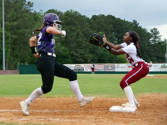 Pineville's Ty Robinson (24, right) tags Denham Springs Rayne Minor (22, left) out at first.