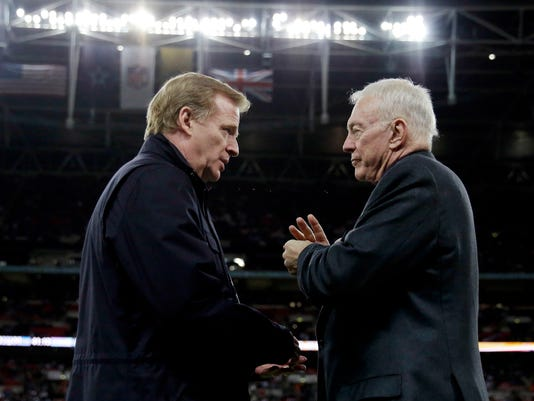 FILE - In this Nov. 9, 2014, file photo, NFL Commissioner Roger Goodell, left, and Dallas Cowboys owner Jerry Jones talk at the NFL football game between the Jacksonville Jaguars and the Cowboys at Wembley Stadium in London. Jones has threatened to sue the NFL over a proposed contract extension for Goodell, a dispute apparently sparked by star running back Ezekiel Elliott's six-game suspension over alleged domestic violence, a person with knowledge of the situation told The Associated Press on Wednesday, Nov. 8, 2017. (AP Photo/Matt Dunham, File)