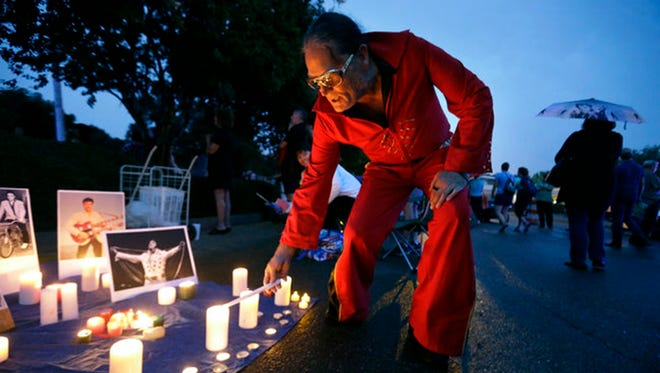 Elvis Whitney, of Denver, Colorado, lights his candle as a light rain begins to fall during Graceland's Elvis Candelight Vigil.