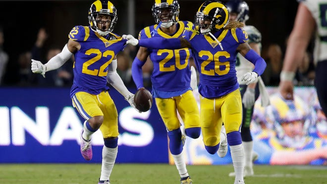 Troy Hill, left, celebrates after his interception with Marqui Christian, right, and Jalen Ramsey during a game against the Seattle Seahawks on Dec. 8 in Los Angeles.