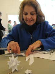 "Kathryn Leiting creates a Moravian star at Ephraim Moravian Church during last year's ""Christmas in the Village."""