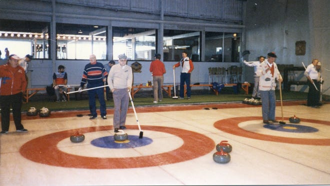 Detroit Curling Club skips Dave Nelsen, left, and Joe Livermore hold brooms as targets for their teams during the November 1986 exchange against the Kitchener-Waterloo Granite Club at the DCC's clubhouse, which was then in West Bloomfield.