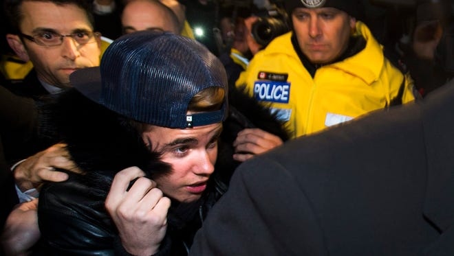 Justin Bieber is swarmed by media and police officers as he turns himself into city police for an expected assault charge, in Toronto, on Jan. 29, 2014.