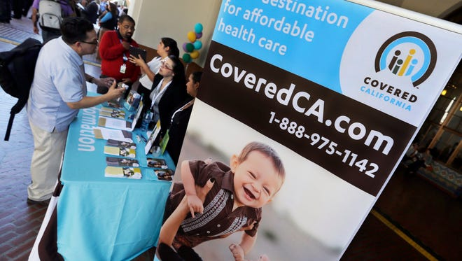 In this Oct. 1, 2013, file photo, an information table is busy at Union Station in downtown Los Angeles as people seek information on state-provided health insurance.