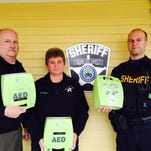 Grand Isle County Sheriff Ray Allen, left, along with Lt. Donna Polk and Sgt. Blake Allen show off three of the 10 AEDs now used by the department.