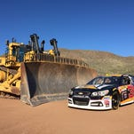 A Caterpillar bulldozer, which can be operated with remote controls, is shown next to a NASCAR vehicle to demonstrate its size.