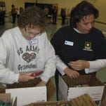 Sheila Furrey and Lori Trunk help pack boxes for soldiers.