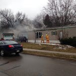 Smoke pours from a mobile home at a park on Avenue A in Springfield on Wednesday morning. Two people escaped the fire.