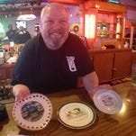 Sports Club co-owner Matt Benjamin shows off some of the collector plates donated by restaurant customers.