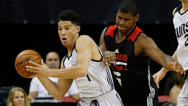 Phoenix Suns' Devin Booker, left, and Chicago Bulls' Cristiano Felicio battle for the ball during the first half of an NBA summer league basketball game Saturday, July 18, 2015, in Las Vegas. (AP Photo/John Locher)