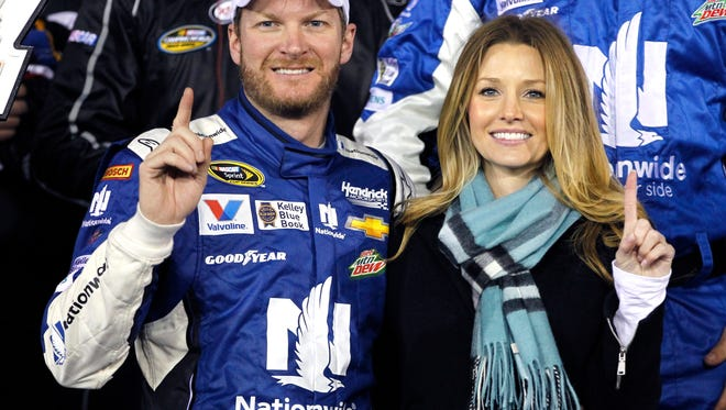 Dale Earnhardt Jr, left, poses with girlfriend Amy Reimann, right, in Victory lane after winning the first of two qualifying races for the Daytona 500 NASCAR Sprint Cup series auto race at Daytona International Speedway in Daytona Beach, Fla., Thursday, Feb. 19, 2015.
