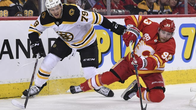 Bruins defenseman Jeremy Lauzon works to knock off Flames left wing Sam Bennett from the play during a February game.