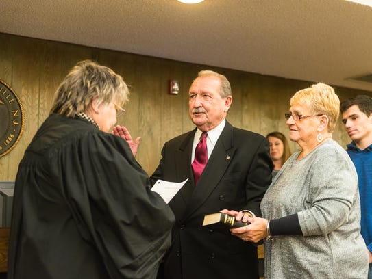 W. James Parent is sworn into the Millville City Commission by retired New Jersey Superior Court Judge Georgia Curio at a meeting Tuesday night at City Hall on Tuesday. Parent stands with his wife by his side.