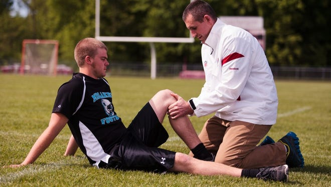 Dr. Christopher Brown works on an injured athlete.