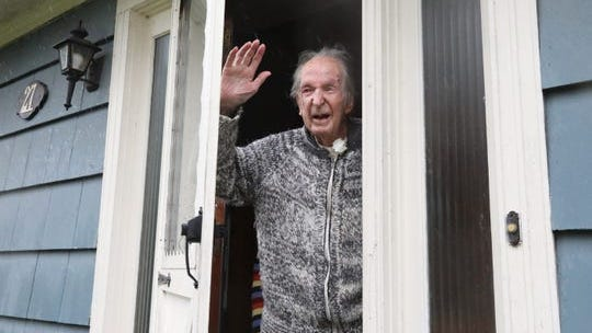 Alan Cameron waves to people driving by his Pearl River home to congratulate him on his 101st birthday April 13, 2020.