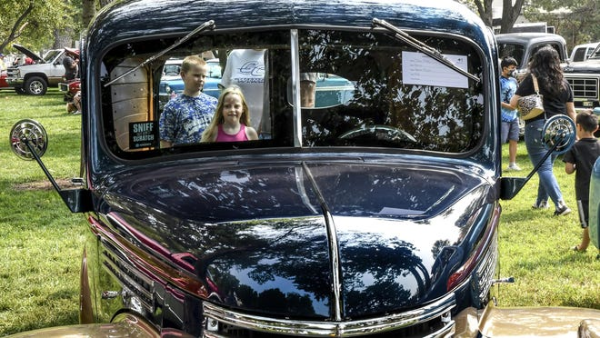 Mason Roark, 9, left and his sister, Molly, 6, check out the interior of a 1946 Chevy panel truck from an open rear door Saturday while attending the Summer Daze car show with their family in Stevens Park.