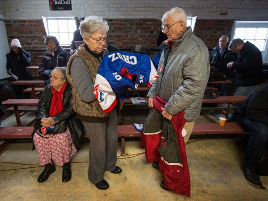 Virginia and Ron Ogan of Osceola put on Cruz jerseys before the arrival of Republican presidential candidate U.S. Sen. Ted Cruz at High Point Bulls Oswald Barn near Osceola, Iowa, at 9:23 a.m. Tuesday Jan. 26, 2016.