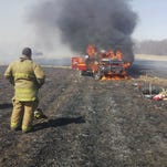 """Firefighters from the Liberty Volunteer Fire Department watch as their truck known as the """"grass rig"""" burns on April 1, 2015."""