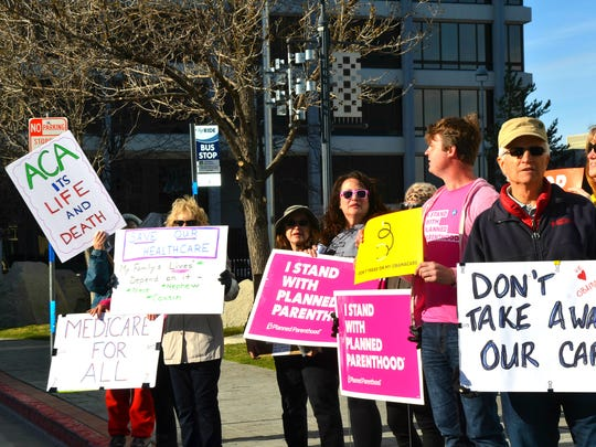 A handful of people gather outside the federal courthouse on Thursday to protest against the bill that would replace Obamacare.