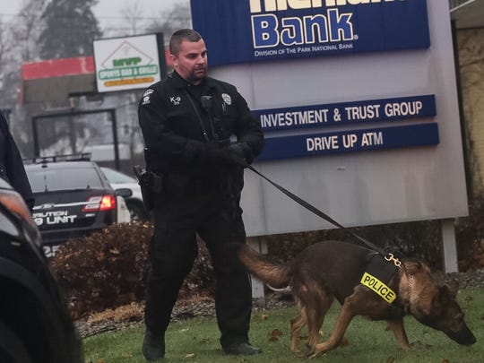 Mansfield police Officer Korey Kaufman and a police  dog investigate the scene of a robbery at Richland Bank on Marion Avenue.
