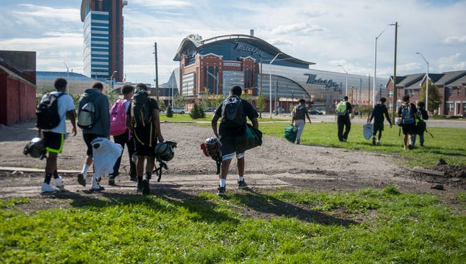 Cass Tech football players walk to practice on Sept. 27, 2016. Due to the field at the high school being grass the football team must was close to a mile to another field to practice.