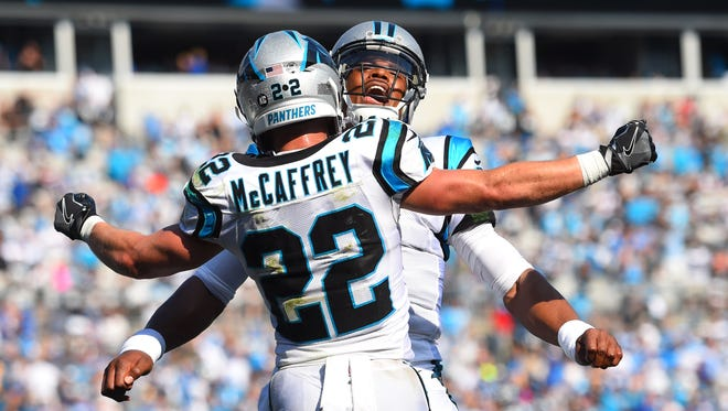 Carolina Panthers running back Christian McCaffrey celebrates with quarterback Cam Newton after scoring a touchdown in the fourth quarter at Bank of America Stadium in Charlotte, N.C.