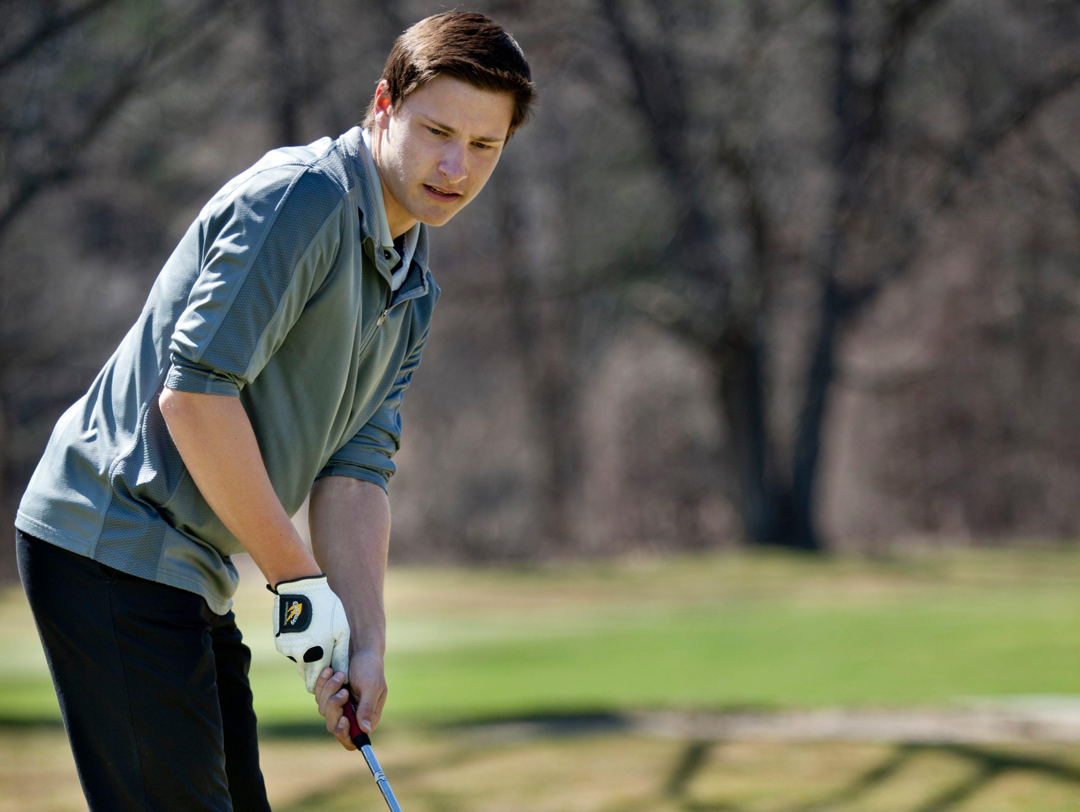 Marysville junior Seth Lewis, 18, sinks a putt Friday at the Port Huron Elks Golf Club in Port Huron Township.