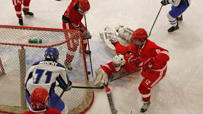 North Rockland goalie Kenny Hoppe blocks a shot by Pearl River's Tommy Murphy (71) with help from Trent Kirschkel (12) in the first period Sunday at Sport-O-Rama in Monsey.