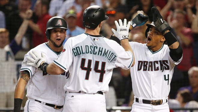 Arizona Diamondbacks first baseman Paul Goldschmidt (44) is congratulated by David Peralta (6) and Ketel Marte (4) after hitting a three-run home run against the Colorado Rockies during the first inning of the National League wild card game at Chase Field in Phoenix, Ariz. October 3, 2017.
