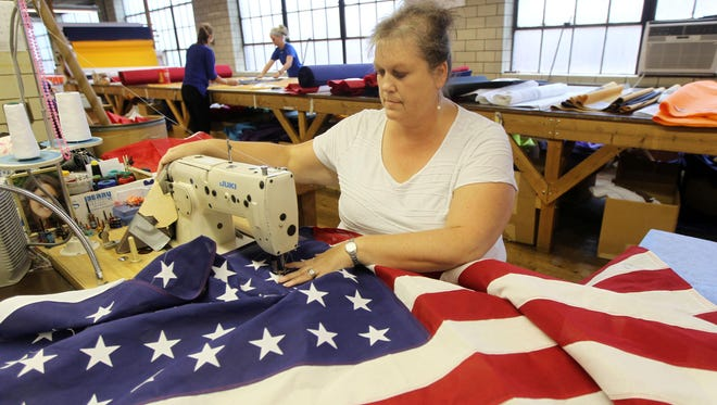 Susan Collins, a stitcher at National Flag Co. for 31 years, sews stars on a 48-star American flag that will be used in a movie.