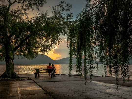 A couple sits beneath a tree on the Peekskill riverfront.
