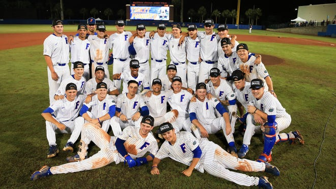 Florida celebrates with a group photo after they defeated Auburn in an NCAA Super Regional college baseball game Monday in Gainesville.