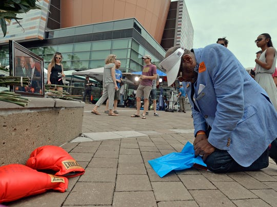 Frank Green, of Louisville, Ky., kneels to pray at a memorial for Muhammad Ali on Saturday at the Muhammad Ali Center in Louisville. Ali died Friday at 74.